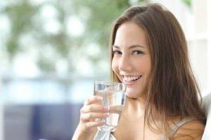 chica bebiendo agua de purificador de agua